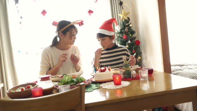 Mother and daughter are eating a feast at Christmas party