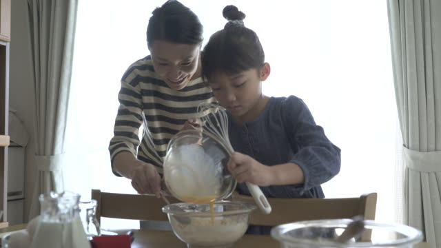 mother and daughter are making homemade cookies together - two generation family stock videos & royalty-free footage
