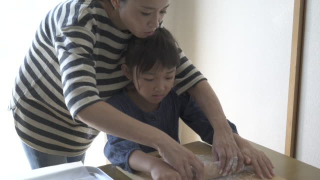 vídeos de stock, filmes e b-roll de mother and daughter are making homemade cookies together - rolo de pastel