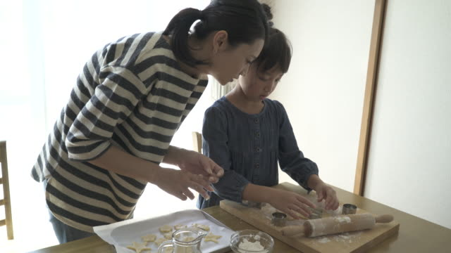 mother and daughter are making homemade cookies together - スイーツ点の映像素材/bロール