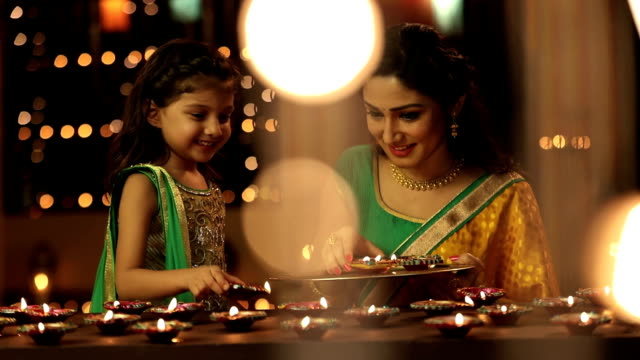ms pan mother and daughter arranging diyas during diwali festival - 焦点点の映像素材/bロール