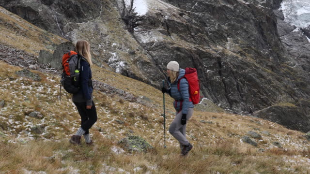 Mother and daughter ascend mountain slope after snowfall