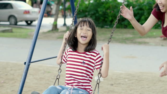 mother and daughter asian swinging at a public playground. - swinging stock videos & royalty-free footage
