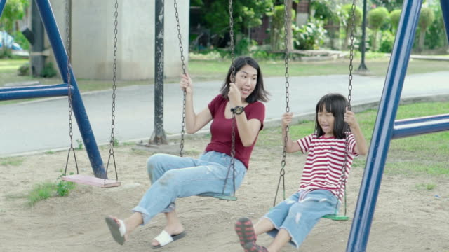 mother and daughter asian swinging together at a public playground. - swinging stock videos & royalty-free footage