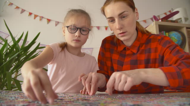 mother and daughter assembles big bright puzzle at the table - puzzle stock videos & royalty-free footage