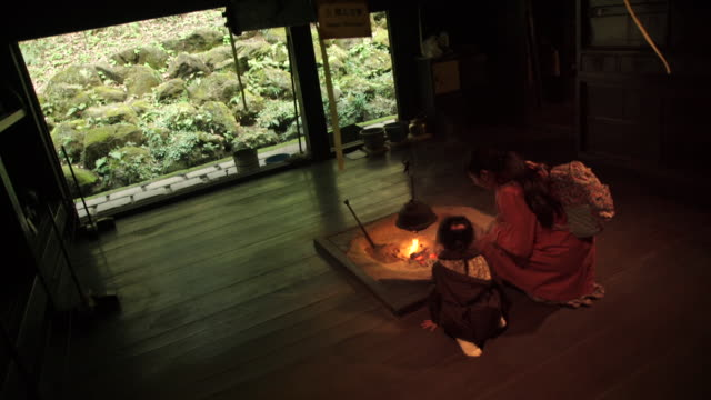 mother and daughter at fire pit in traditional home - japan - 暖炉点の映像素材/bロール