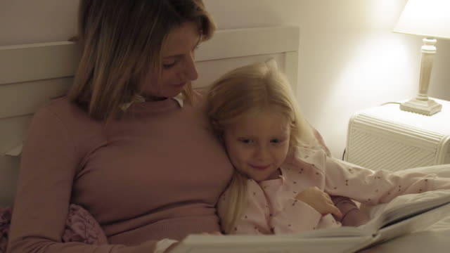 mother and daughter at home at bedtime reading story - ora di andare a letto video stock e b–roll