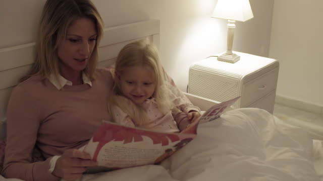 Mother and daughter at home at bedtime reading story