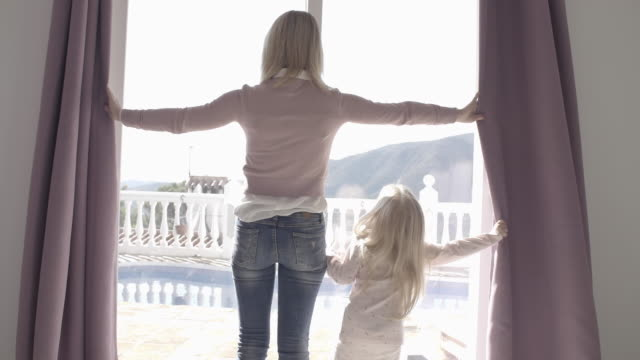 Mother and daughter at home opening curtains in morning