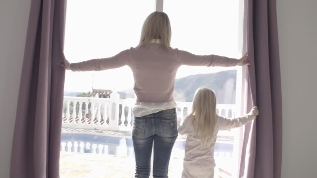 vidéos et rushes de mother and daughter at home opening curtains in morning - regarder par la fenêtre