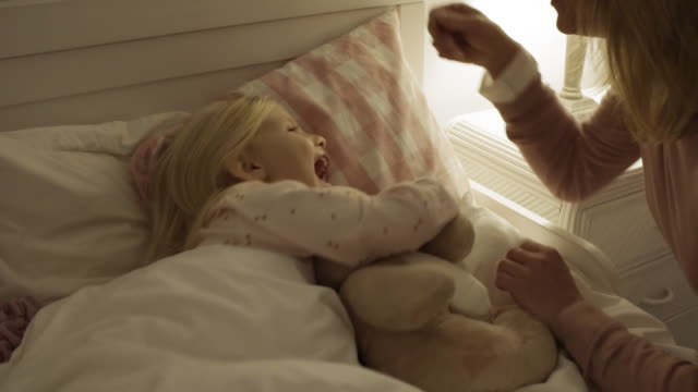 mother and daughter at home putting little girl to bed with teddy bear - ora di andare a letto video stock e b–roll
