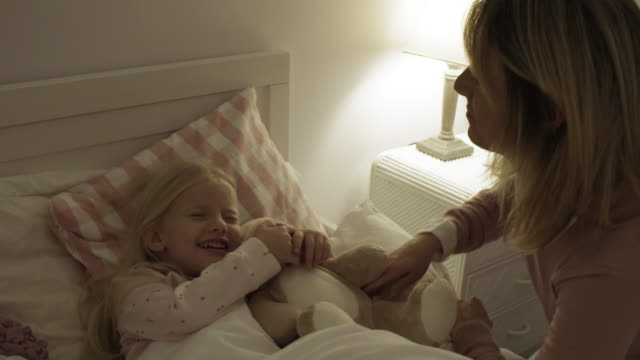 Mother and daughter at home putting little girl to bed with teddy bear