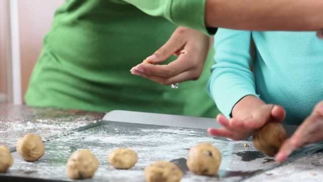 cu td mother and daughter baking chocolate chip cookies in kitchen / richmond, virginia, usa - クッキー点の映像素材/bロール