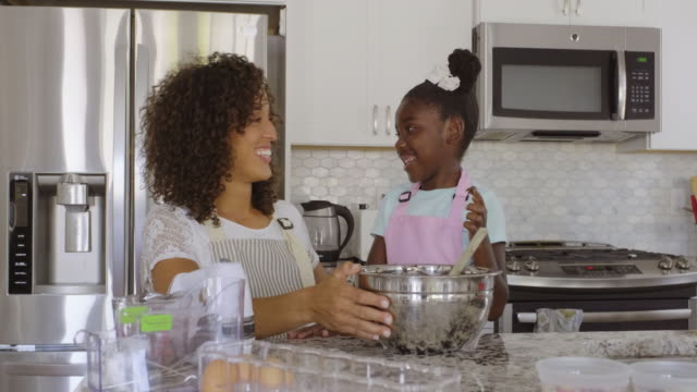 mother and daughter baking cupcakes in a home kitchen - daughter stock videos & royalty-free footage