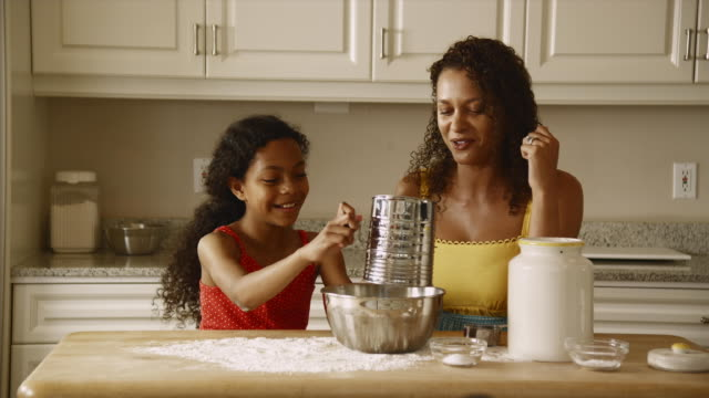 ms mother and daughter (12-13) baking in kitchen / edmonds, washington state, usa - pacific islander family stock videos & royalty-free footage