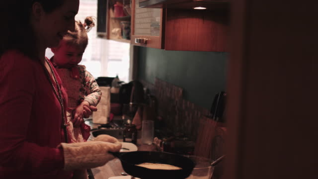 mother and daughter baking pancake at home - mitten stock videos and b-roll footage