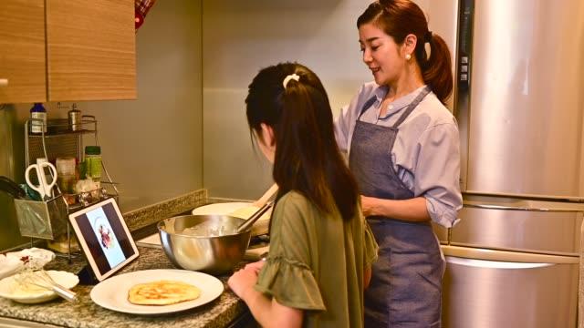 タブレットでレシピを見ながらパンケーキを焼く母と娘。 - 電化製品点の映像素材/bロール