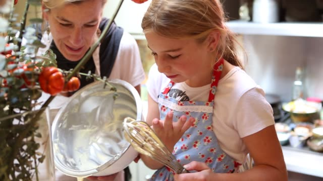 mother and daughter baking together in kitchen - wire whisk stock videos and b-roll footage