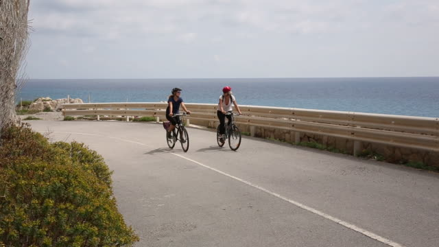 mother and daughter bicycle along sea promenade - sports helmet stock videos and b-roll footage