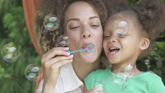 mother and daughter blowing bubbles - curly hair stock videos & royalty-free footage