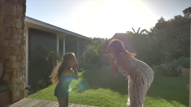 vidéos et rushes de mother and daughter blowing kisses - patio