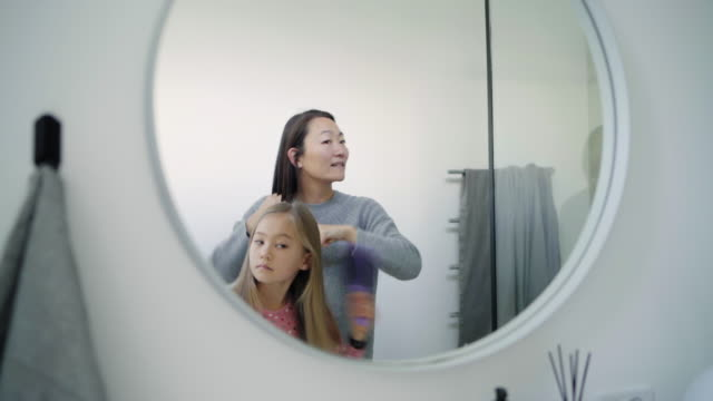 stockvideo's en b-roll-footage met mother and daughter brushing hair - haarborstel
