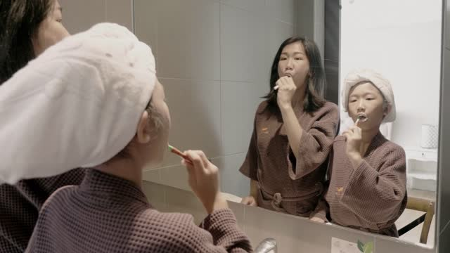 vídeos y material grabado en eventos de stock de madre e hija cepillando sus dientes juntos en el baño de casa. - cepillar los dientes