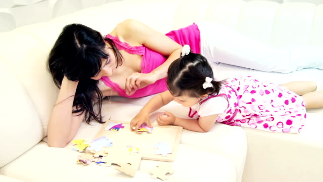 stockvideo's en b-roll-footage met mother and daughter building a puzzle - puzzel