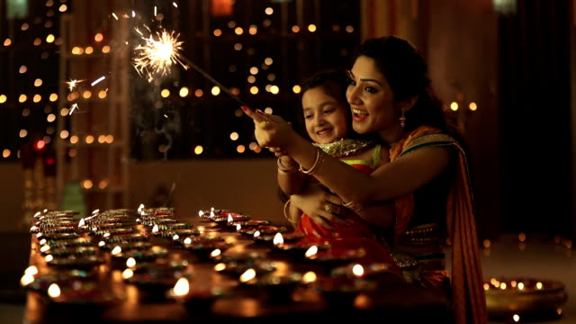 ms pov mother and daughter burning sparkler during diwali festival - india stock videos & royalty-free footage