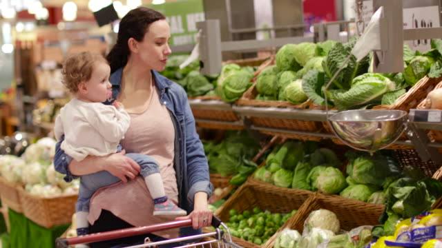 Mother and daughter buying vegetables in grocery store