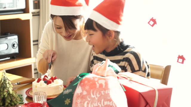 mother and daughter catiing cake at christmas party - ケーキ点の映像素材/bロール