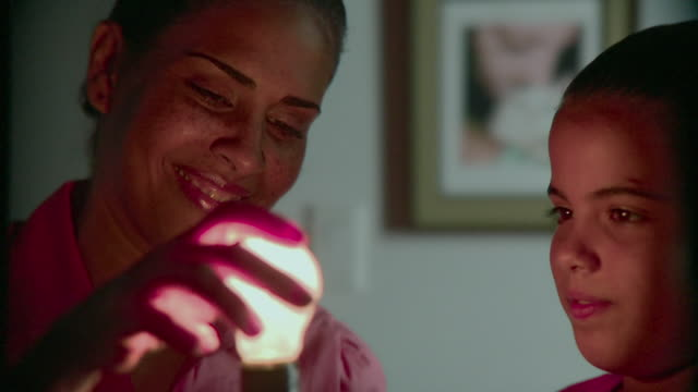 vídeos de stock, filmes e b-roll de cu mother and daughter (8-9) changing bulb for energy efficient bulb in lamp, panama city, panama  - variação