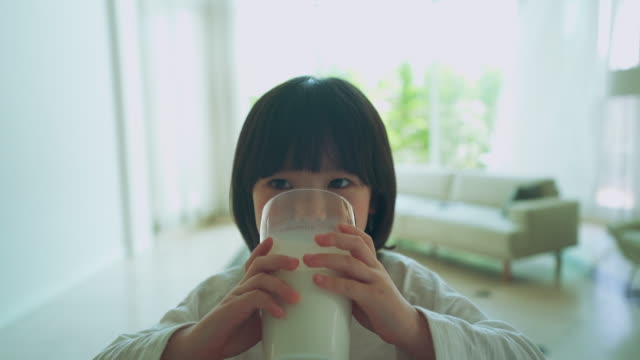 mother and daughter, child drinking milk in the living room - kindertag stock-videos und b-roll-filmmaterial
