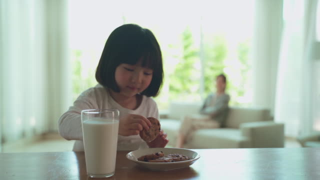 mother and daughter, child eating cookies in the living room - クッキー点の映像素材/bロール