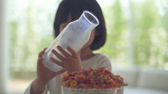 mother and daughter, child pouring milk into a bowl of cereal - kindertag stock-videos und b-roll-filmmaterial