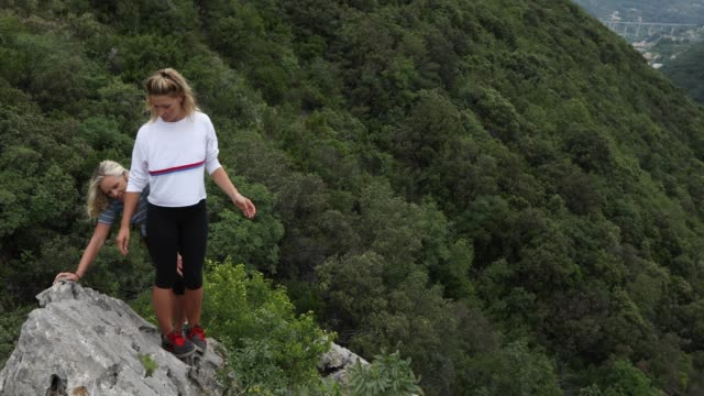 mother and daughter climb rock ridge, above valley - 55 59 anni video stock e b–roll