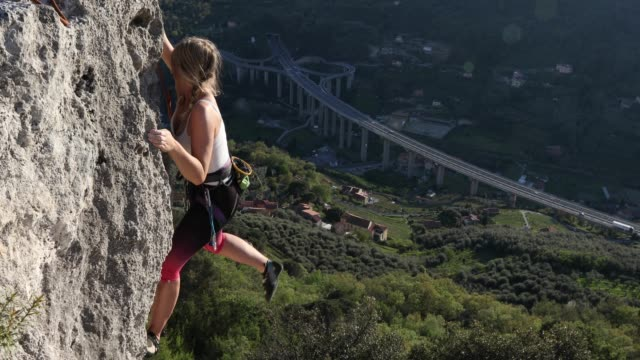 mother and daughter climb vertical rock cliff - trovare video stock e b–roll