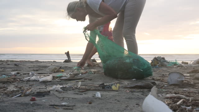 vídeos de stock e filmes b-roll de mother and daughter collect garbage on beach, sunrise - limpar