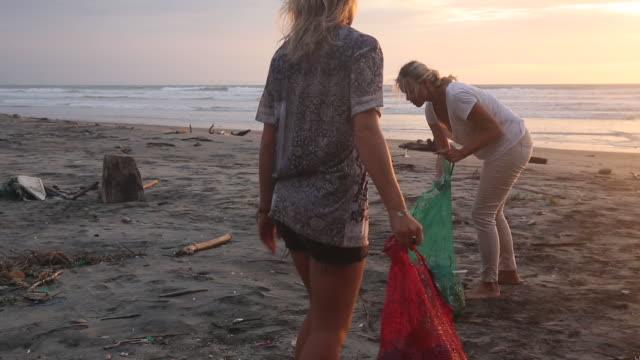 mother and daughter collect garbage on beach, sunrise - pulizia dell'ambiente video stock e b–roll