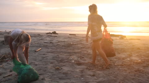 mother and daughter collect garbage on beach, sunrise - cleaning stock videos & royalty-free footage