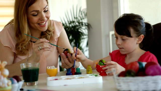 Mother and daughter coloring Easter eggs at home