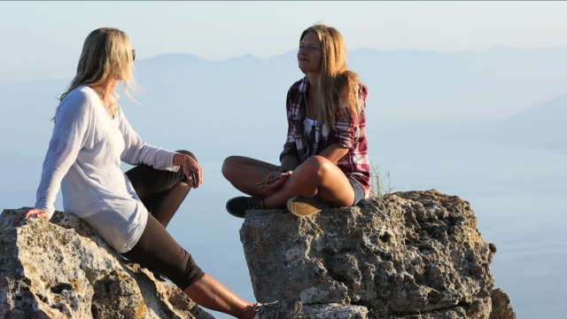 """""""mother and daughter converse on rocks, take picture"""" - girl sitting cross legged stock videos & royalty-free footage"""