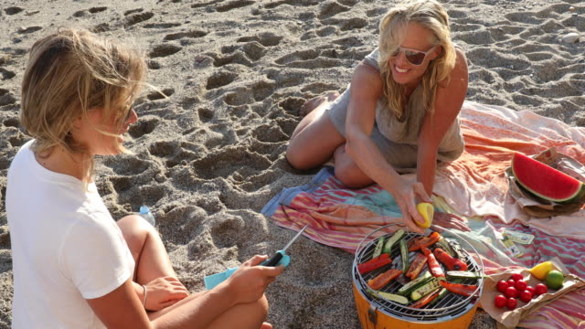 Mother and daughter cook vegetables over bbq, at beach