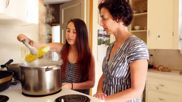 vídeos y material grabado en eventos de stock de ms mother and daughter cooking corn on stove in home kitchen - cámara en mano