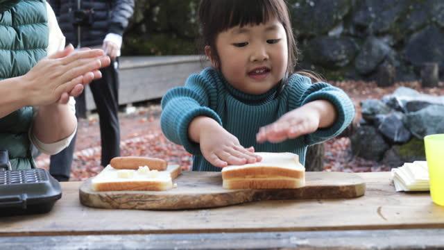 vidéos et rushes de mother and daughter cooking outdoors - sandwich