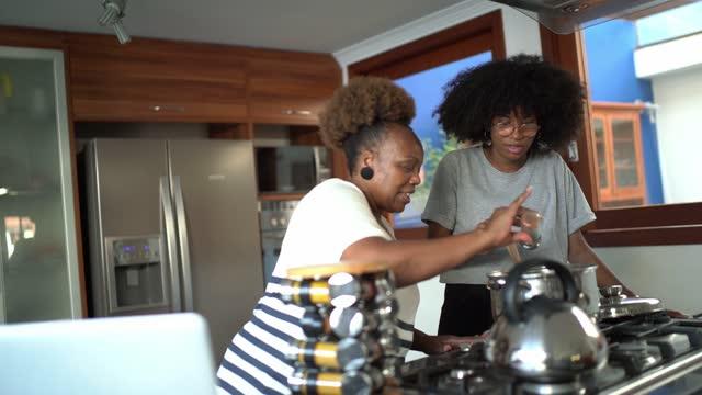 vídeos de stock, filmes e b-roll de mãe e filha cozinhando juntas em casa - cozinha