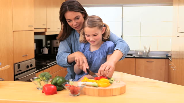 mother and daughter cooking together - haarzopf stock-videos und b-roll-filmmaterial