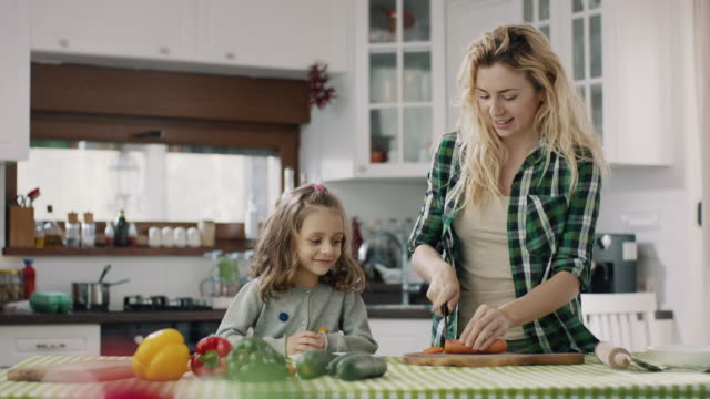 vídeos de stock e filmes b-roll de mother and daughter cooking together - cenoura