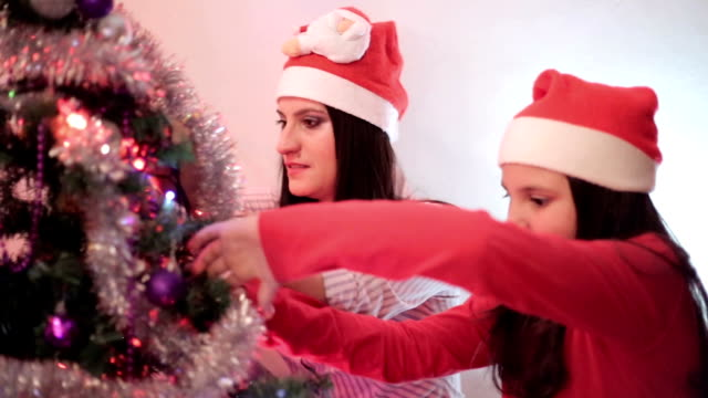 mother and daughter decorate a christmas tree - little girls flashing stock videos and b-roll footage