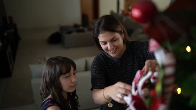vídeos de stock, filmes e b-roll de matriz e filha que decoram a árvore de natal e que abraçam em casa - filha
